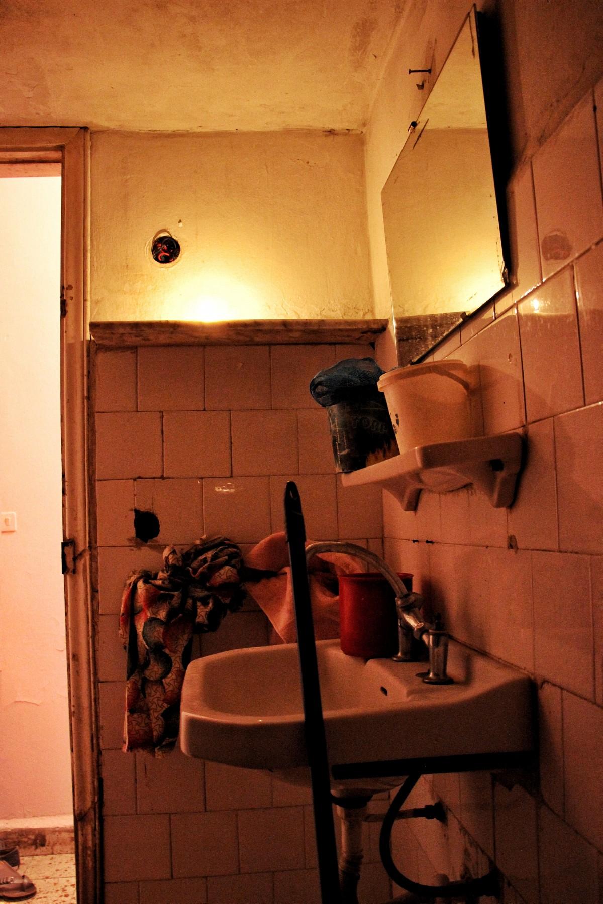 Dans les appartements des travailleuses domestiques II, salle de bain éclairée à la bougie